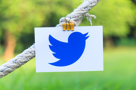 Bangkok, Thailand - June 15, 2017: Twitter logo sign printed on paper hanging on a rope in the park. Twitter is an online social networking popular social media.