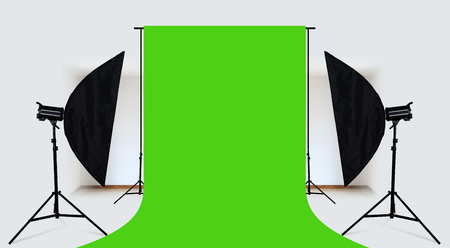 Photo studio with lighting equipment and green backdrop