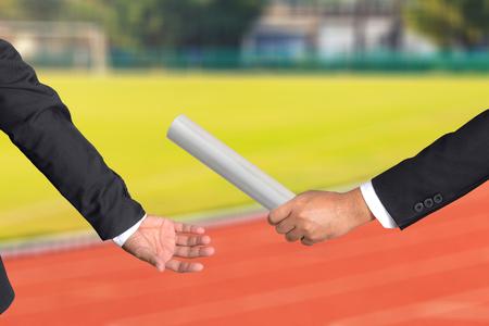 Bebouwde de hand van zakenman passerende estafettestokje naar collega, het concept van teamwork voor zakelijk succes