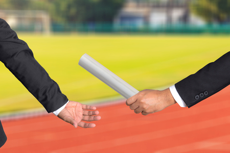 baton: Cropped hand of businessman passing relay baton to colleague, the concept of teamwork for business success