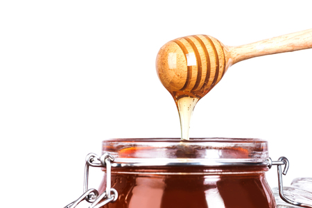drizzler: Glass jar of Honey with wooden drizzler on white background