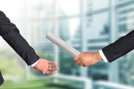 Mão cortada de empresário passando bastão de retransmissão para colega, o conceito de trabalho em equipe para o sucesso empresarial