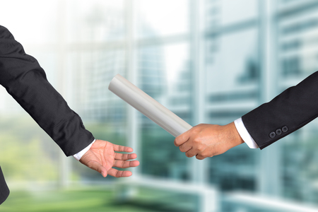 Cropped hand of businessman passing relay baton to colleague, the concept of teamwork for business success