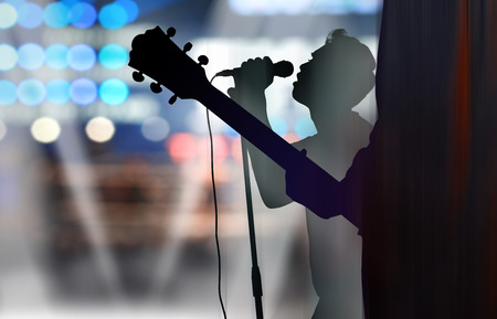 Silhouette of electric guitar player and singer under spotlight on a stage, live in concert Stock Photo
