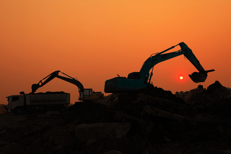 Silhouette of Excavator loader in construction site at sunset sky background