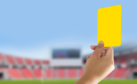 Referee showing yellow card in the field Stock Photo