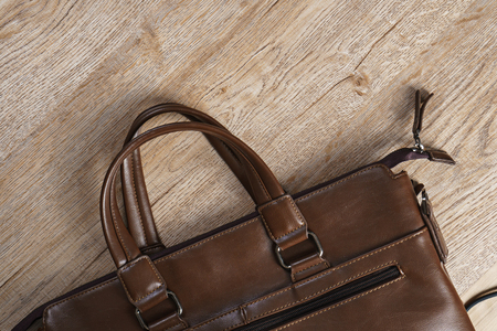 Leather bag on wooden board background