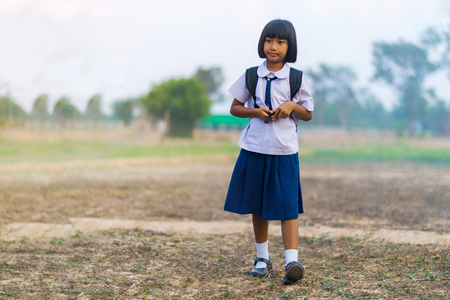 Asian student in uniform studying at countryside of Thailand Standard-Bild