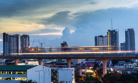 Light line of the Skytrain in city downtown with blue sky and clouds at Bangkok, Thailand