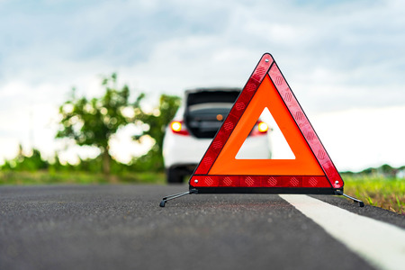 Problems car and a red triangle warning sign on the road 版權商用圖片 - 107343799