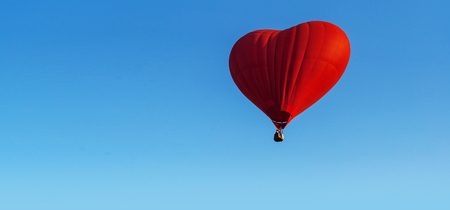 Red heart balloon on blue sky