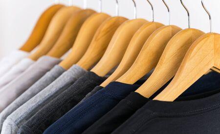 Cerca de camisetas en perchas, fondo de prendas de vestir