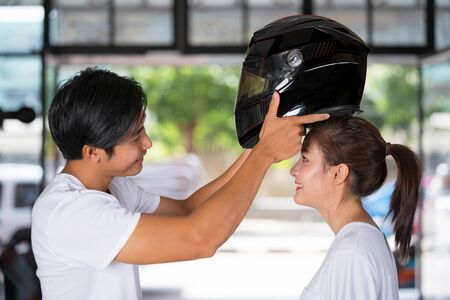 Traveling couple standing and wearing a motorcycle helmet