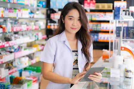 Asian female pharmacist uses digital tablet in the pharmacy