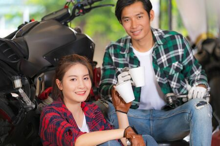 Happy couple drinking coffee at a motorcycle repair shop and a motorcycle background