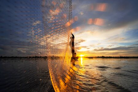 Silhouette of Fisherman on fishing boat with net on the lake at sunset, Thailand Stock Photo