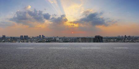 Empty highway asphalt road and city skyline at sunrise background