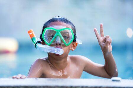 Vista del niño con gafas de natación flotando en la piscina