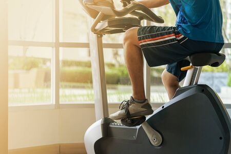 Close up of a man exercise in gym, Cycling on bike in fitness gym