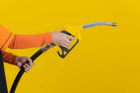 Woman hands holding fuel nozzle isolated on yellow background Stock Photo