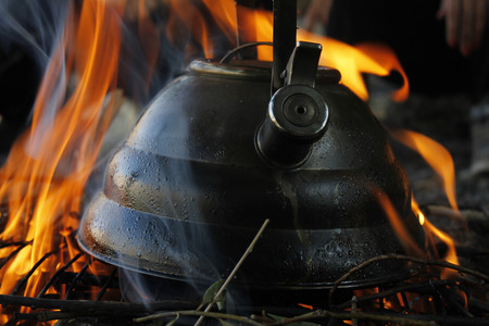 Boiling water in a kettle by fire in a camping photo