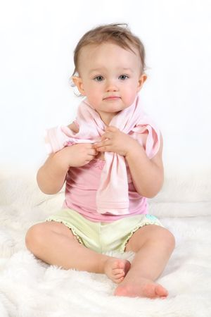 baby girls smiley face: child tries to dress oneself Stock Photo