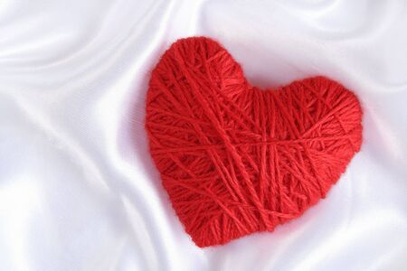 Heart of Yarn on the satin background photo