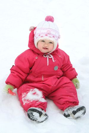 baby girls smiley face: baby girl sitting in the snow Stock Photo