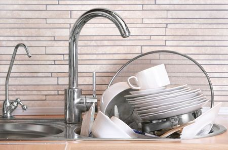 wash dishes: Pile of dirty dishes in the sink