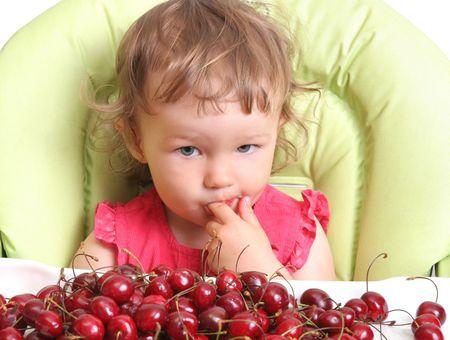 child tastes cherry Stok Fotoğraf