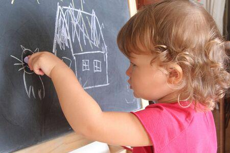 child draws with chalk on the blackboard