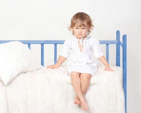 little girl sitting on the bed Stock Photo