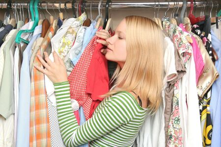 choosing clothes: young female choosing clothes Stock Photo