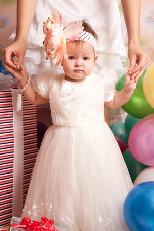 Baby`s first birthday. Mom holding the baby by the hands Stock Photo
