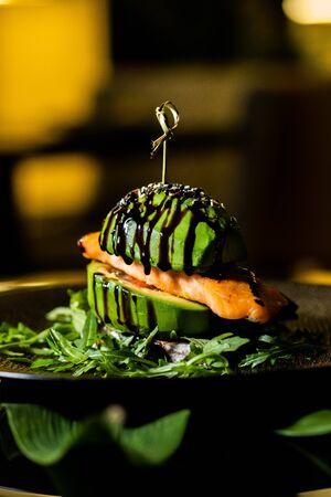 burger, juicy vegan burger, avocado burger, on a black background, fast food, hamburger. Vegan big burger with salmon served on black plate.