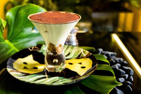 tiramisu in a glass cup with chocolate on a plate. Plate decorated with palm leaves. Фото со стока