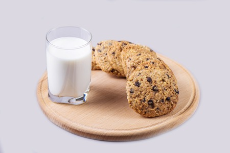 Homemade cookies on a round wooden plate with a glass of milk on a gray background. Delicious sweet present 写真素材