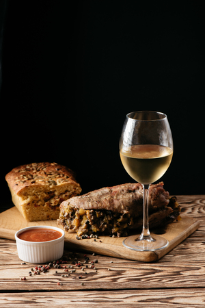 Pumpkin muffin and baked meat roll with filling, along with a sauce on a wooden plate and a glass of white wine on a black background. Dinner