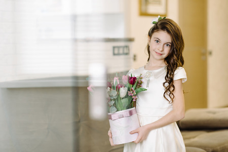 A cute girl sits on a sofa and holds flowers in her hands. Feast day