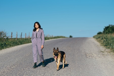 A pretty girl leads a dog next to her on the road.