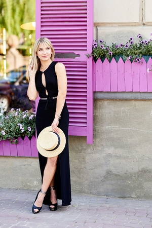 A young, sympathetic blonde in black dress and a straw hat in her hands stands on the background of a window with purple shutters.