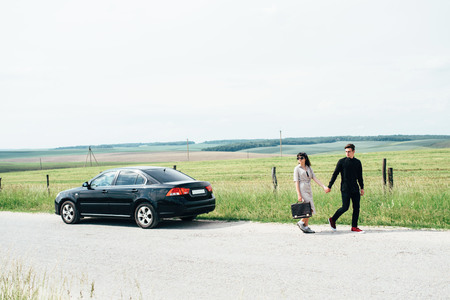 Couple of young girl and boy holding talks near black car on background of blue sky and field.