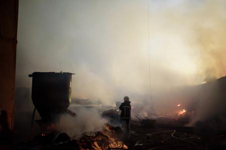 Silhouette of fireman fighting bushfire at night