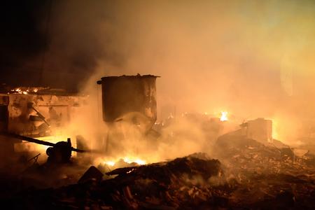 Silhouette of fireman fighting bushfire at night. 免版税图像