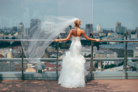 Bride in the morning in a white dress standing on the balcony overlookin the city.