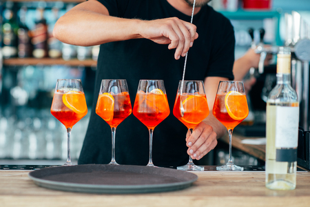 Five colored cocktails prepared by a bartender with pieces of orange and ice cubes. Stockfoto - 116350477