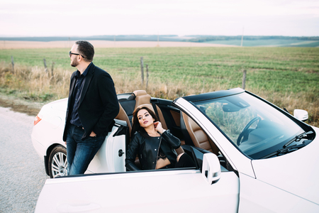 A typical couple of men and women spend time outside the city next to a white car. Stock Photo