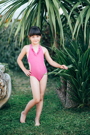 A cute little girl in a pink swimsuit is spending time in the nature in the summer.