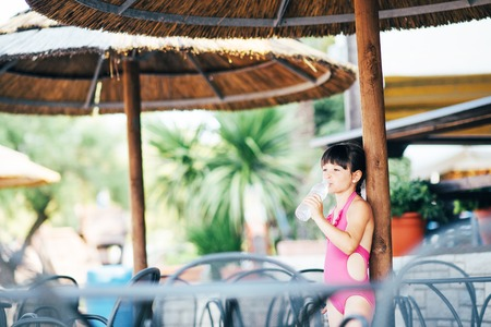 Cute girl in a pink swimsuit in a cafe on the beach in the summer.