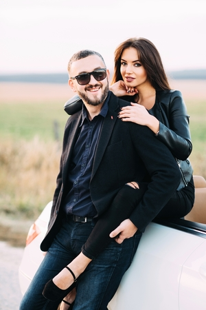 Sympathetic couple husband and wife spend time outside the city, sitting on a car hood. Standard-Bild